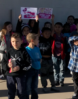 Students in line holding box tops signs.