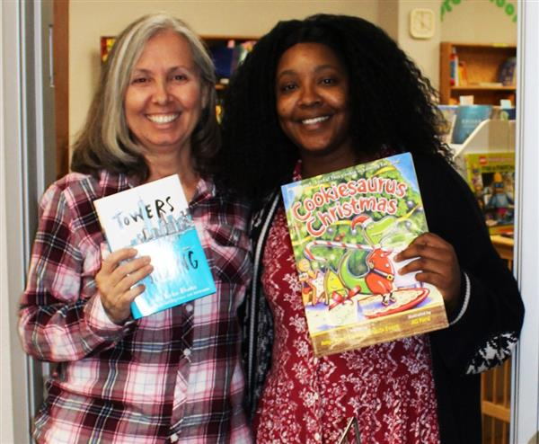 Sky View's Stacy Batiste and Tina Mlodzik receive book donations from the Kids Need to Read nonprofit