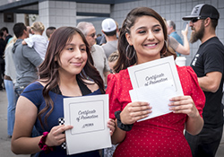 Two female students pose with their elementary promotion certificates