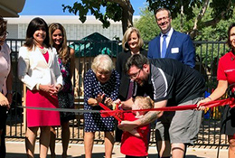 Preschool student cutting ceremonial ribbon while surrounded by district and college staff