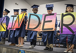 Kindergarten students in graduation robes holding letters that spell out Kinder