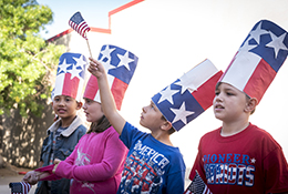 Students wave flags at Veterans Day celebration