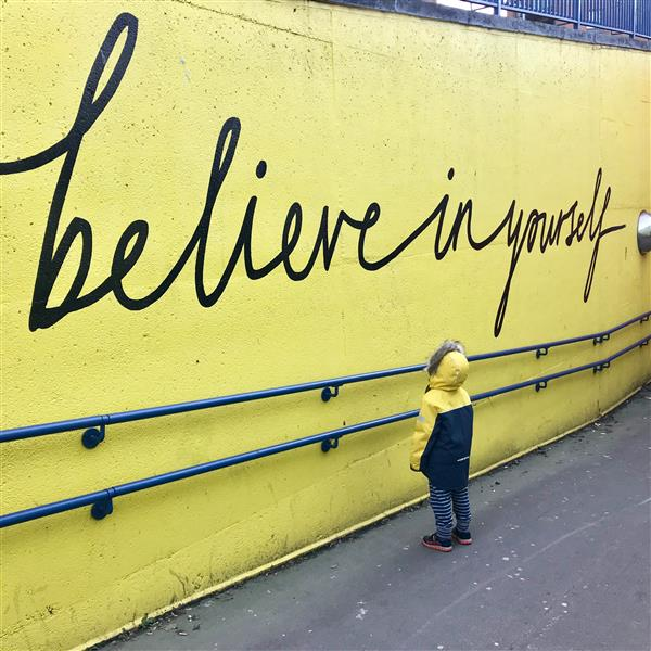 student looking at the words believe in yourself painted on a school wall
