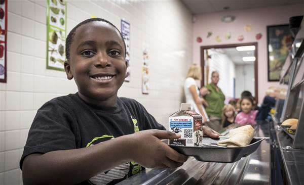 Photo of student in lunch line with chocolate milk on his tray.