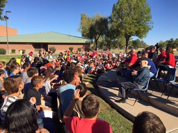 Veterans and students sitting at outdoor assembly